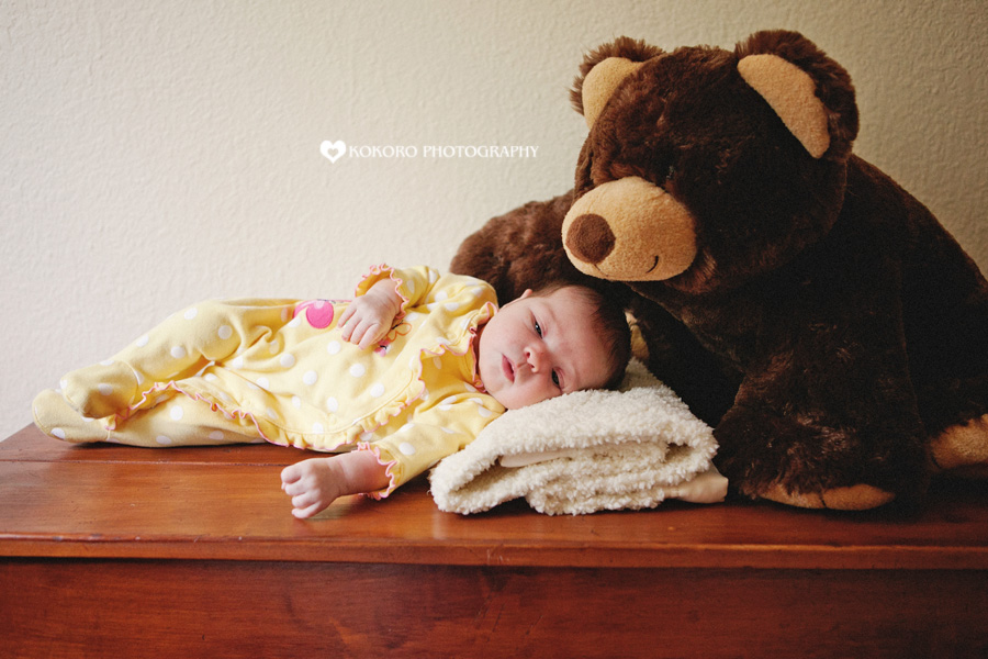 Newborn with shrinking teddy bear